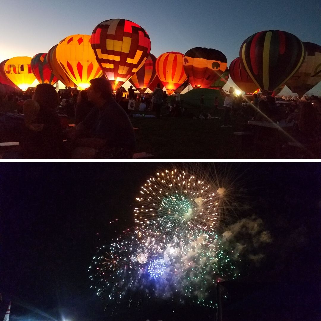 Multiple hot air balloons light up at dusk and a round of fireworks exploding against the night sky