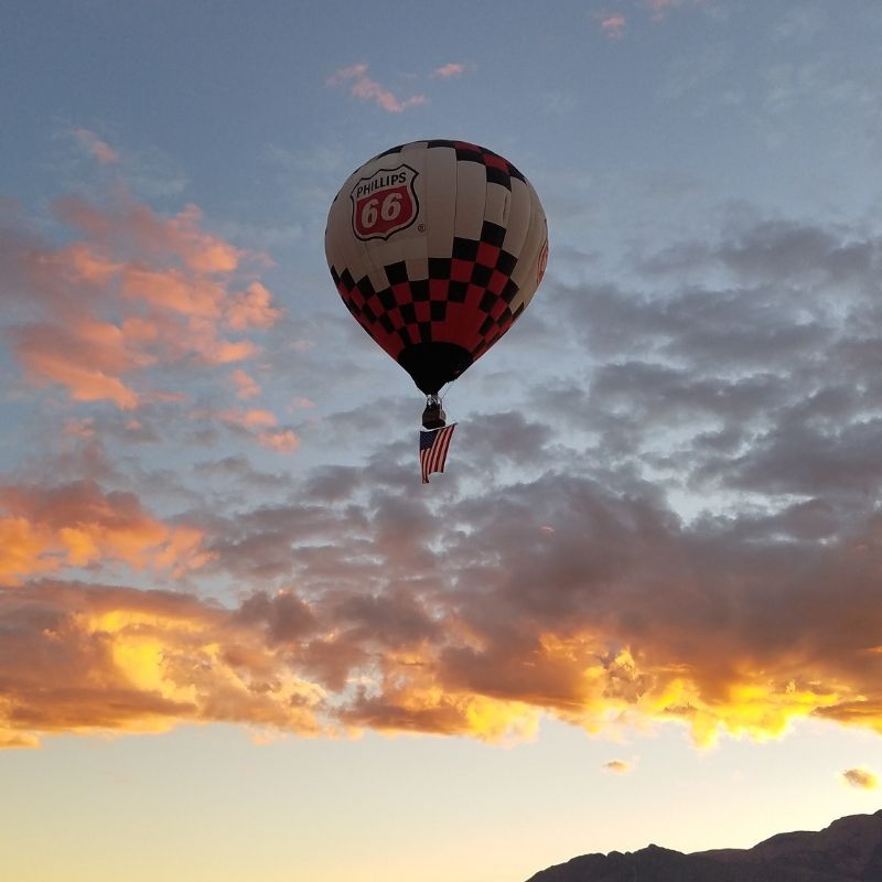 Hot air balloon carries the US Flag across the morning sky