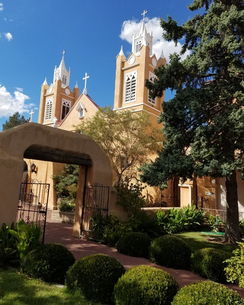San Felipe de Neri Church Steeples and gate with walkway bordered by greenery in Albuquerque New Mexico