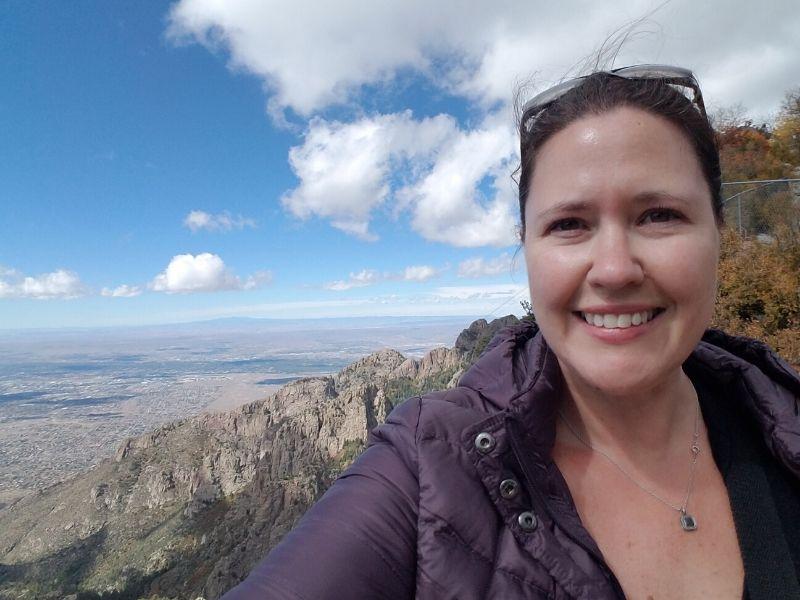 Selfie of woman in purple jacket from the top of Sandia Peak