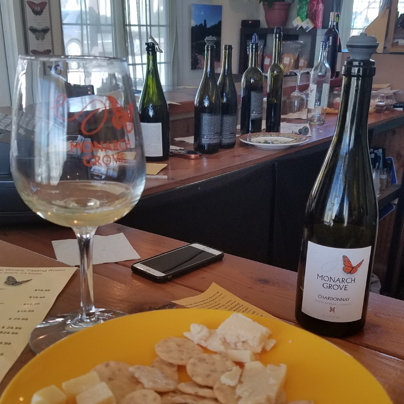 A plate of cheese and crackers alongside a glass of Chardonnay at Monarch Grove Winery