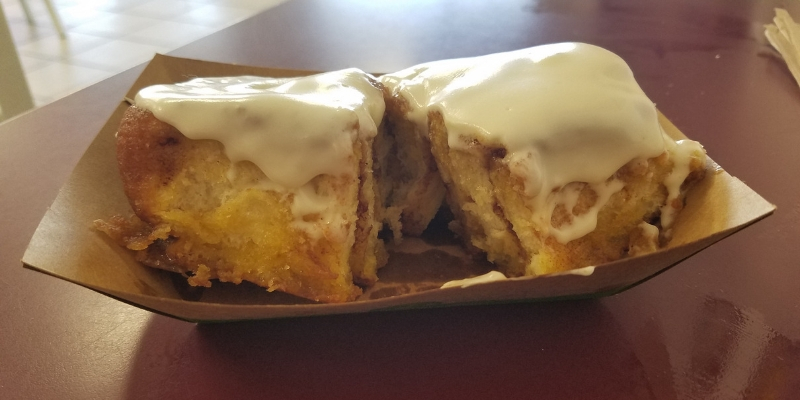 Large cinnamon roll slathered in cream cheese frosting.