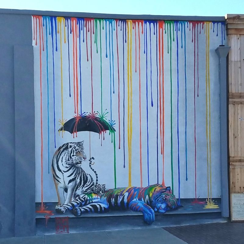Mural Catnap by Michael Summers shows two tigers being rained on by colorful stripes.