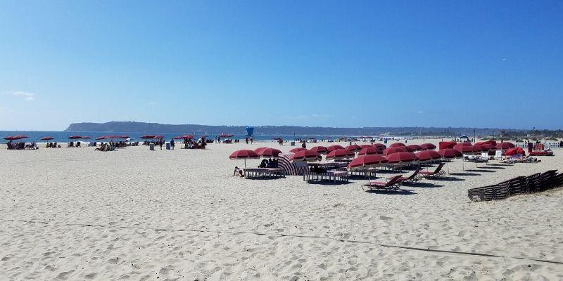 Rows of red umbrellas over beach chairs on Coronado Beach
