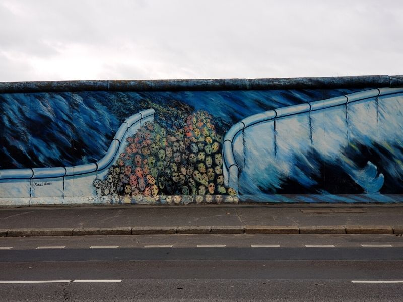 Mural of a crowd going through a wall by Kani Alavi at the East Side Gallery in Berlin