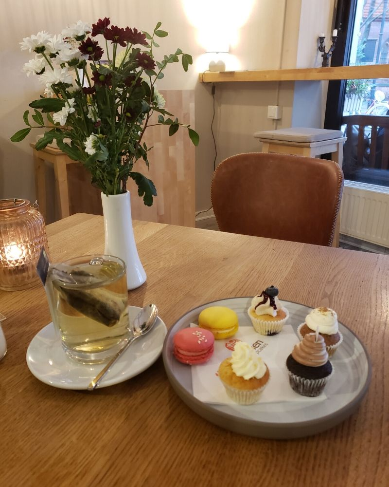 Ginger Tea and a plate of 6 mini cupcakes on a table with a vase of red and white flowers.