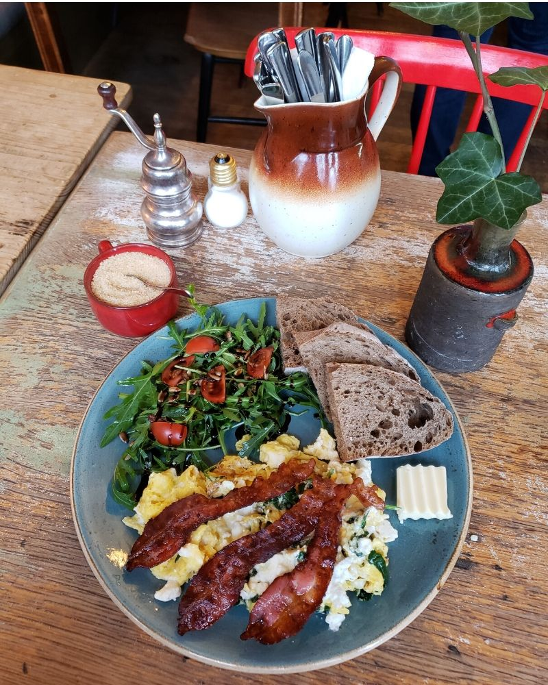 Spinach Feta Bacon Scramble on a blue plate, sitting on a wood table with a plant, pitcher of silverware, salt, pepper, and sugar containers.